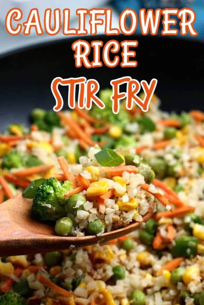 A wooden spoon is holding cauliflower rice stir fry to the camera.