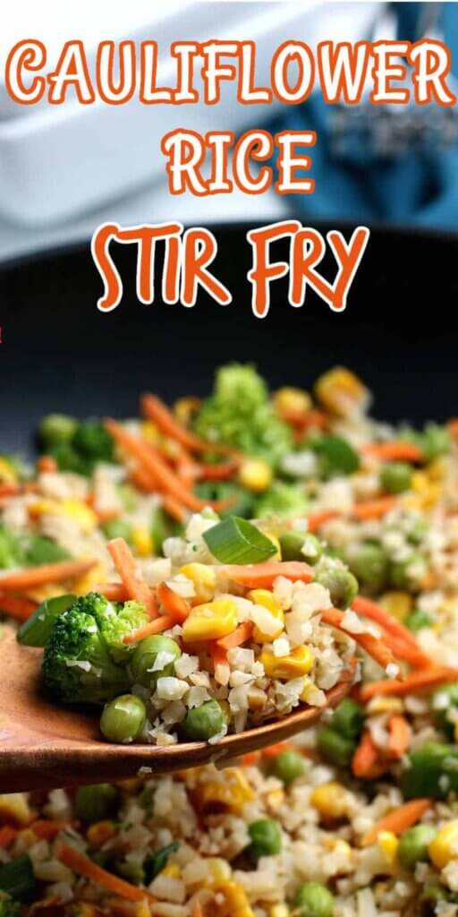 Cauliflower Rice Stir Fry is on a wooden spoon over a full iron pan.