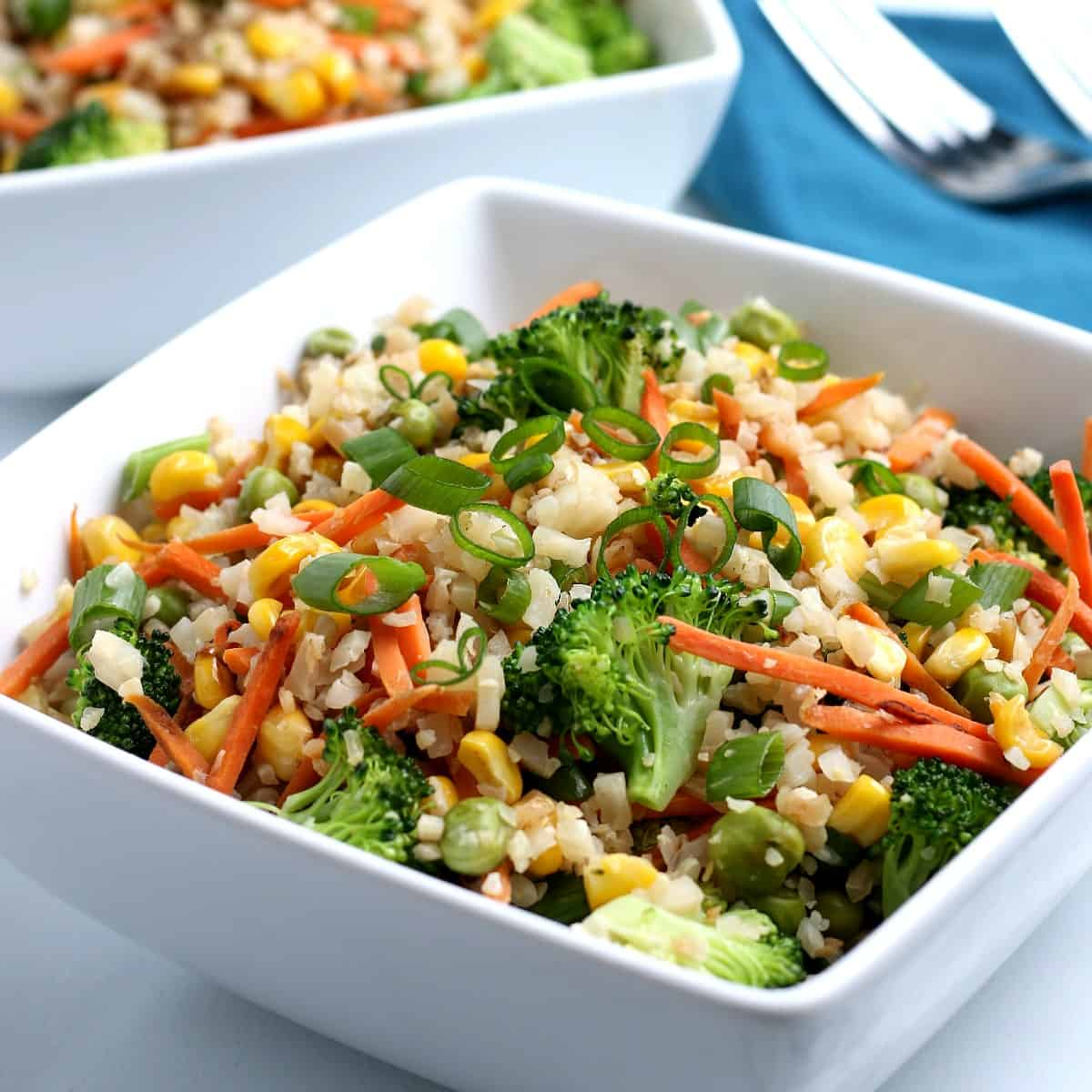 Square white bowl fulled with colorful Cauliflower Rice Stir Fry.