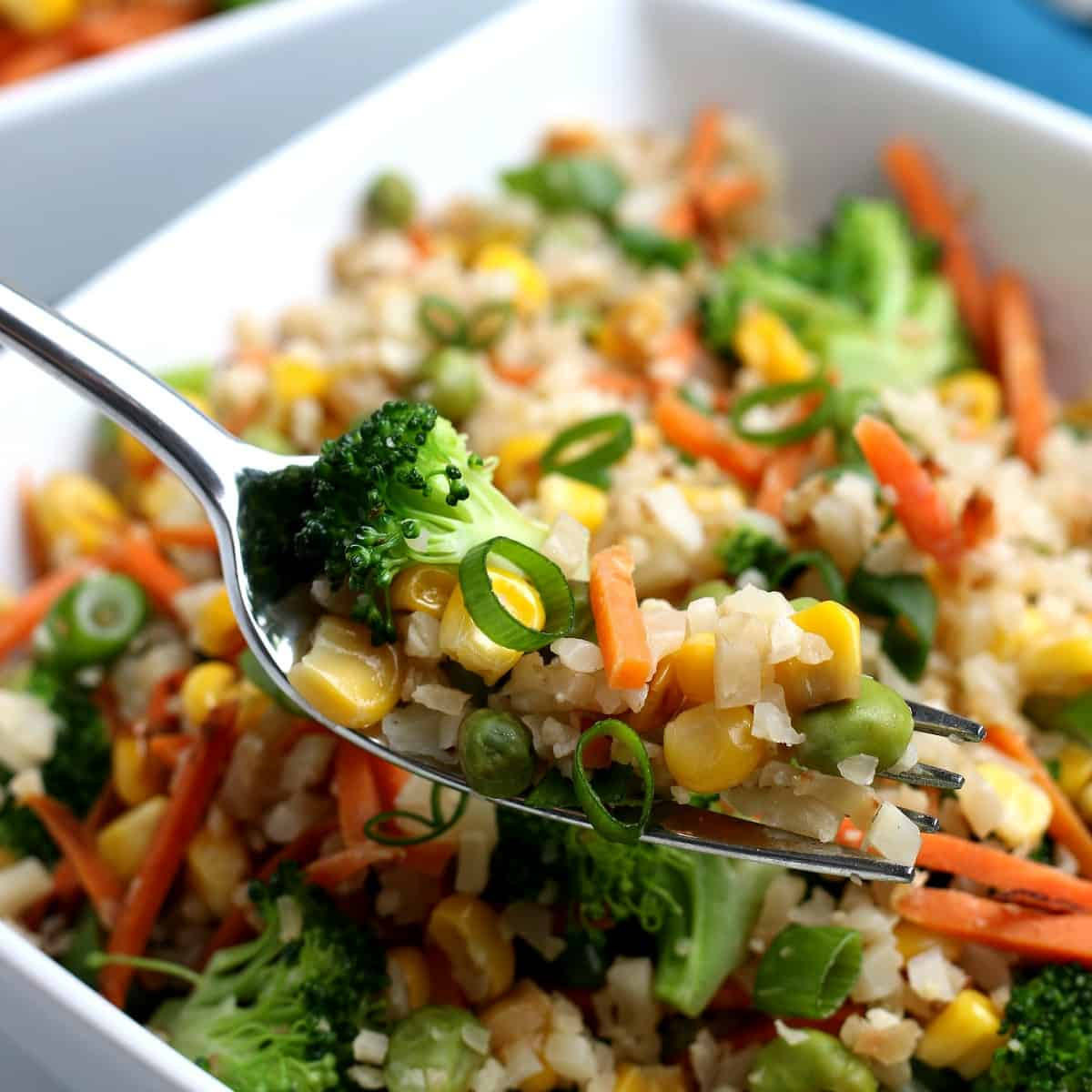 A fork full of mixed veggies is lifted up to the camera lens.