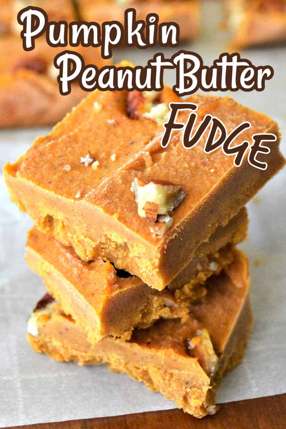 Thre squares of pumpkin fudge stacked on top of each othe with more behind.