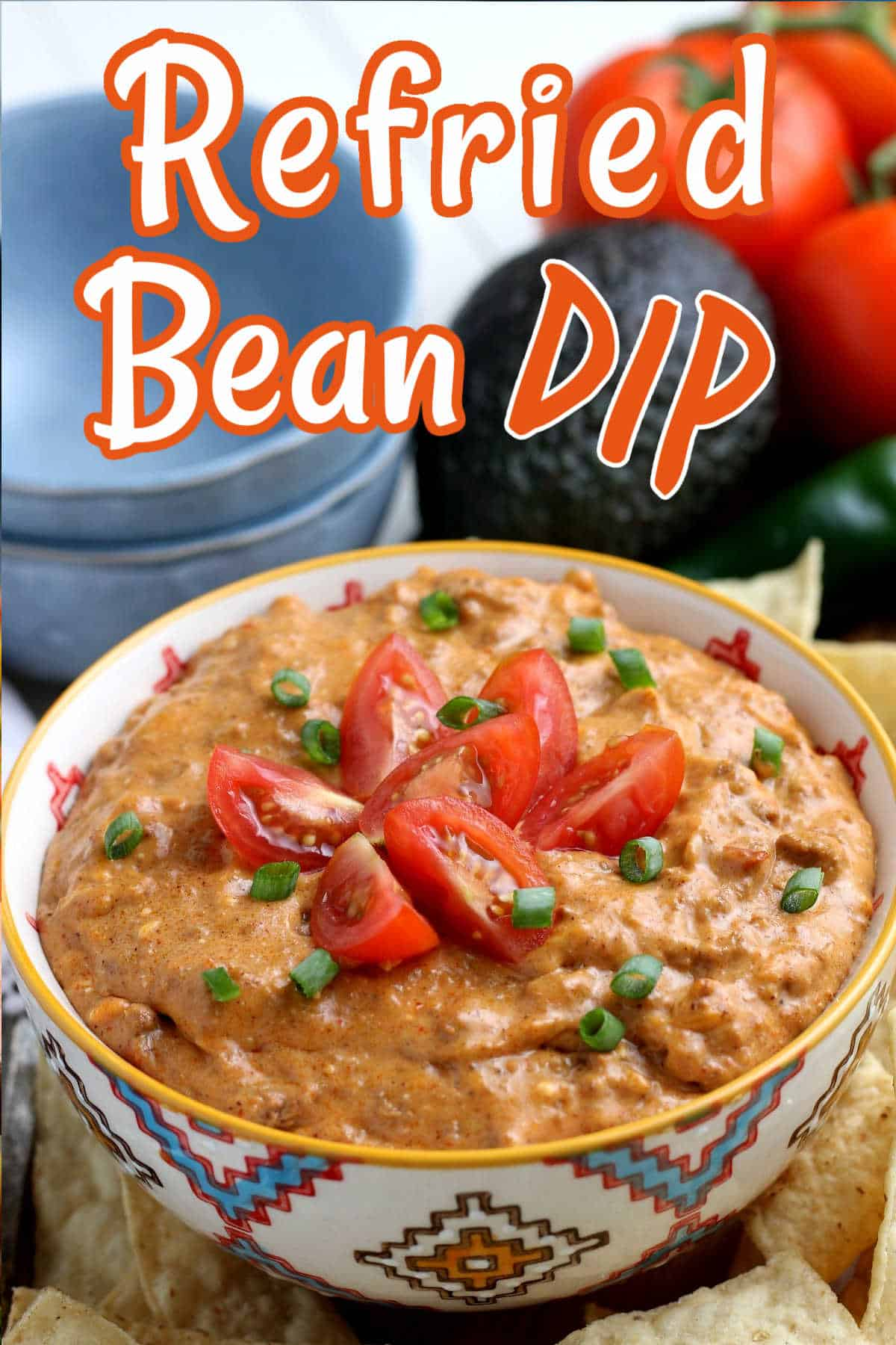 Refried Bean dip is in a bowl with tomato slices and chives on top.