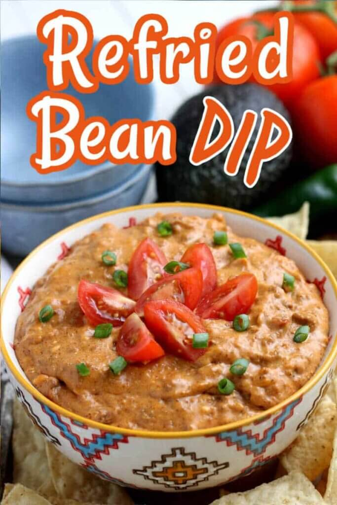 Refried Bean dip is in a bowl and tilted forward with tomato slices on top.