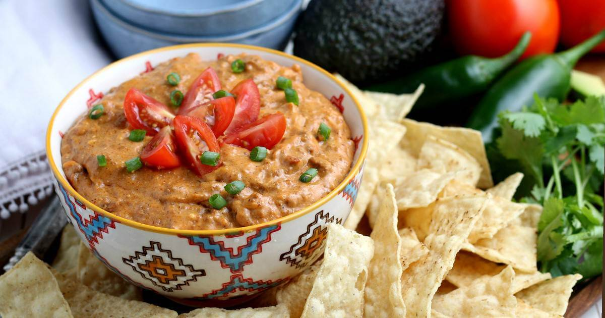 Wide photo of a bowl full of vegan bean dip with tortilla chips on the side.
