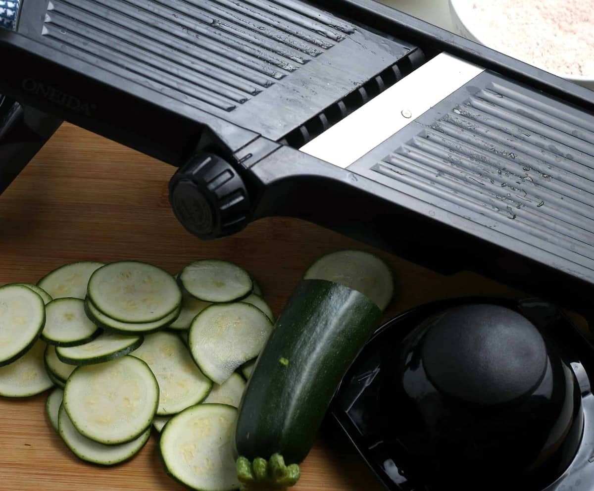 A mandoline, zucchini and veggie slices shown on a cutting board.