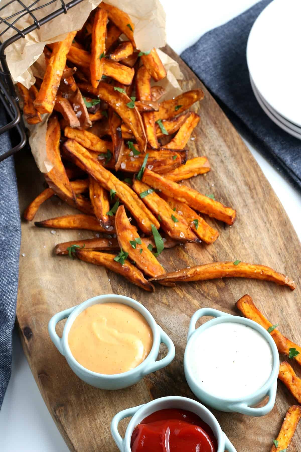 Overhead view of sweet potato fries and three dipping sauces.
