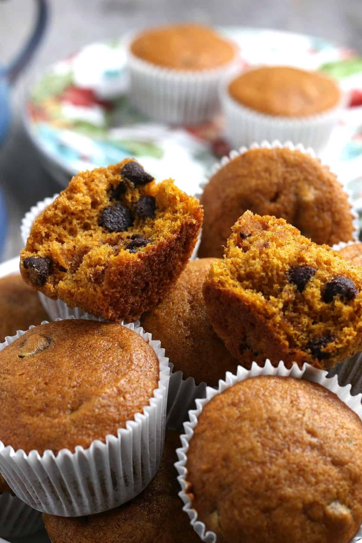 Close up of muffins in paper cups with one open on top of the pile.