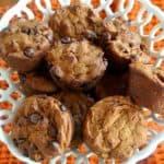 Chocolate chip vegan pumpkin muffins in a opwn weave milk glass basket.