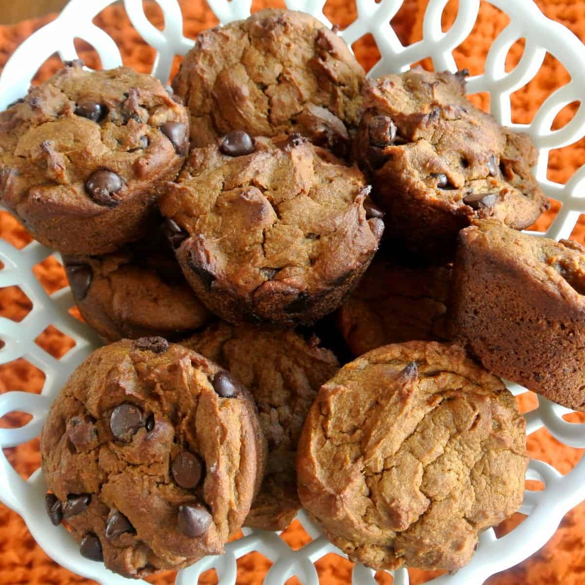 Chocolate chip vegan pumpkin muffins in a opwn weave milk glass basket.