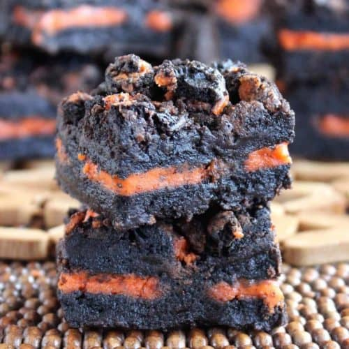 Two orange oreo brownies stacked on top of each other.