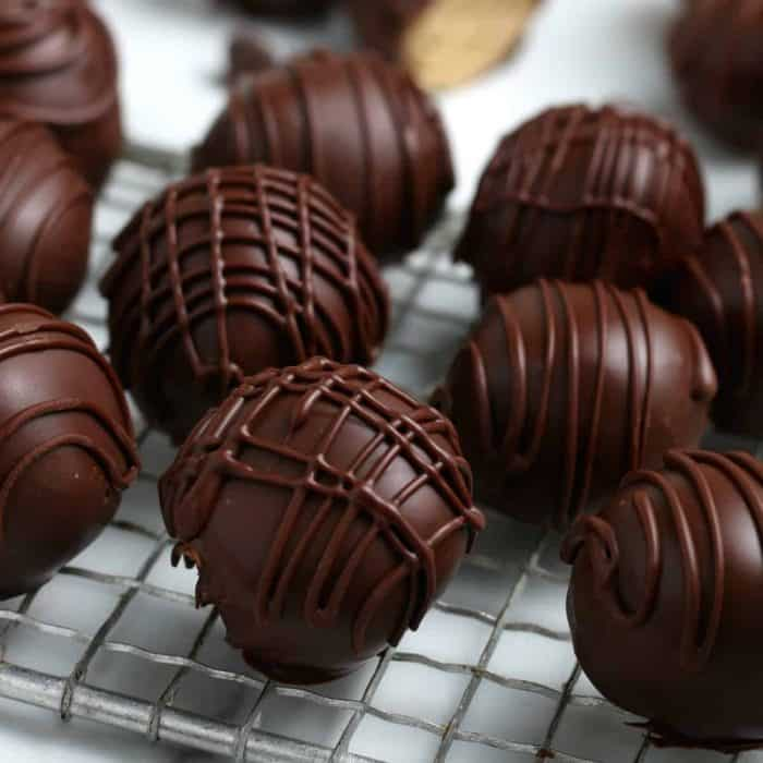 Close up photos of chocolate drizzled peanut butter fudge truffles.