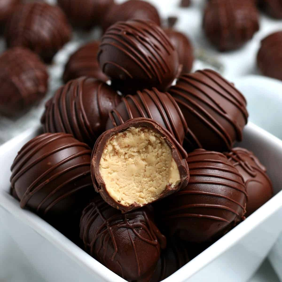 A pile of chocolate covered peanut butter truffles in a white bowl.