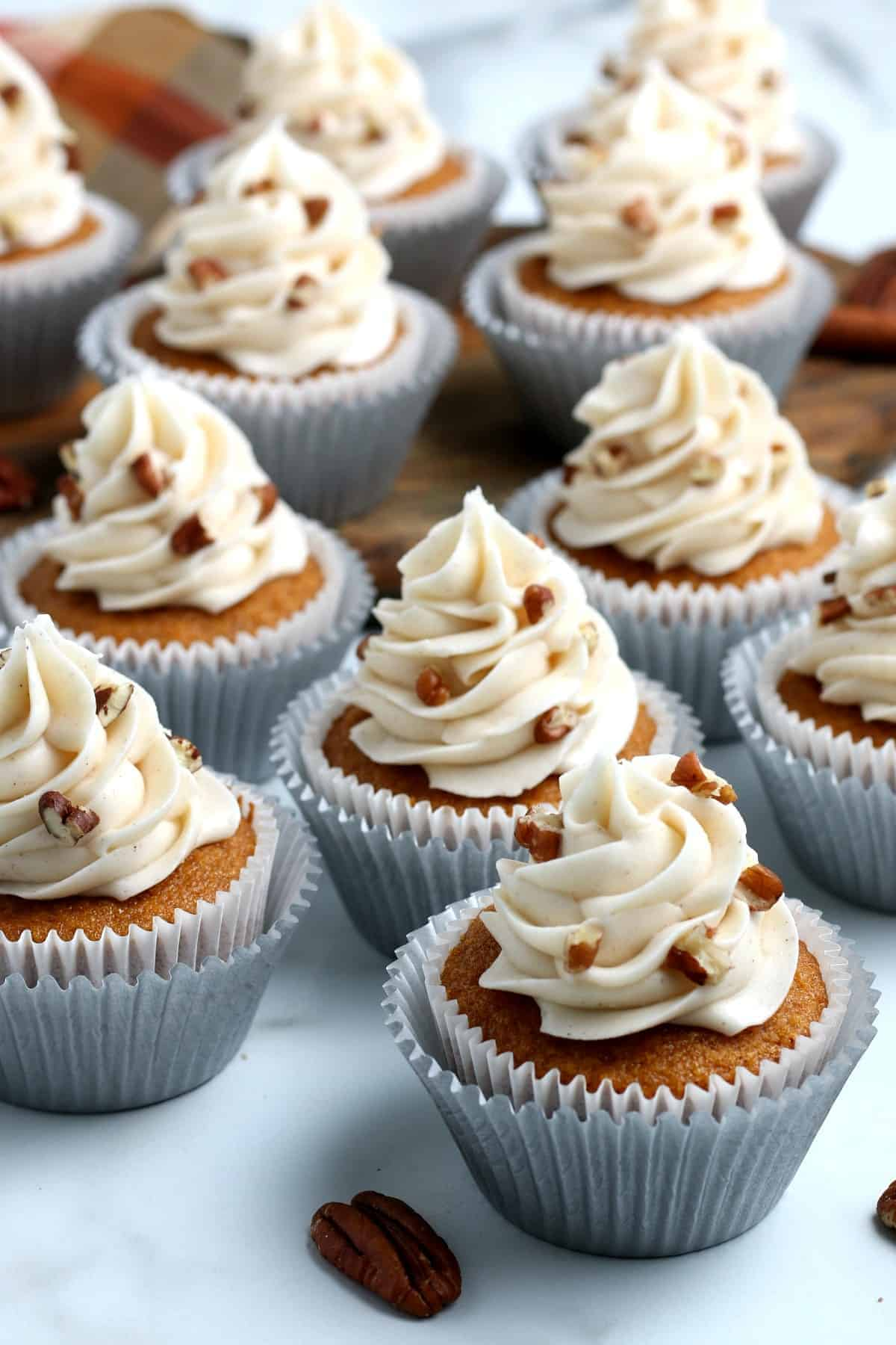 Long view of multiple frosting topped vegan pumpkin muffins.