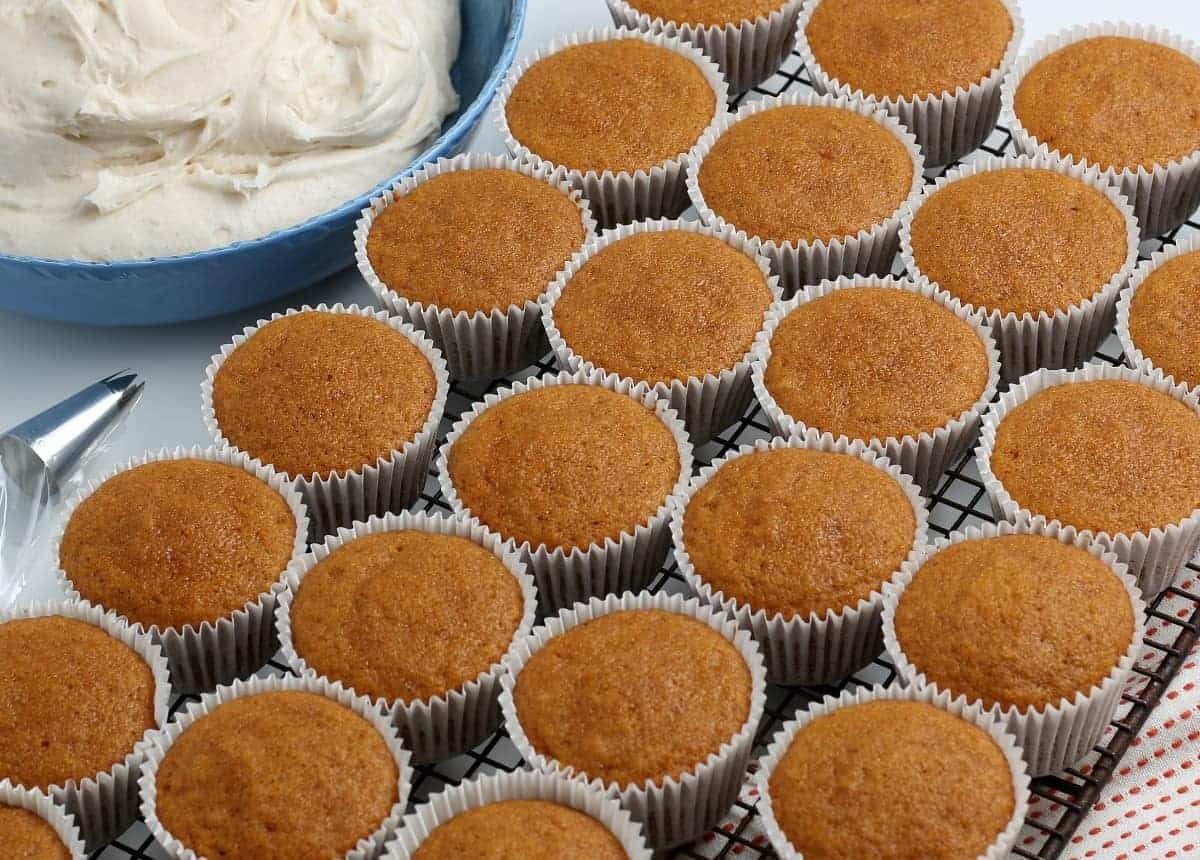 Pumpkin cupcakes straight out of the oven and cooling in a rack.
