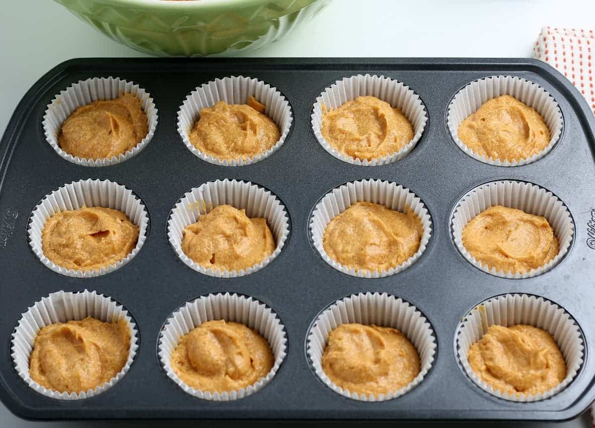 Overhead photo of raw batter filling 12 cupcake paper cups in a tin.