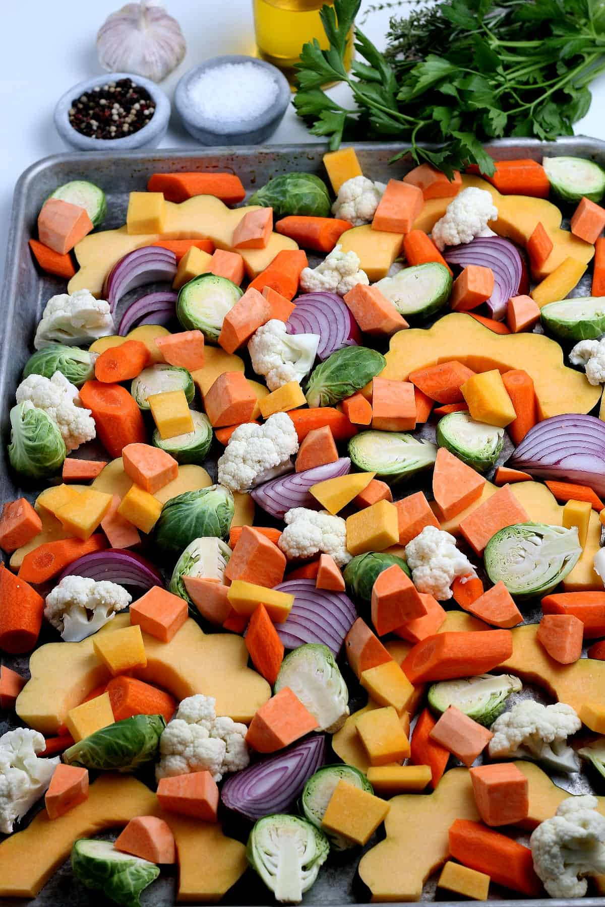 Colorful ingredients spread out on a baking sheet to roast.