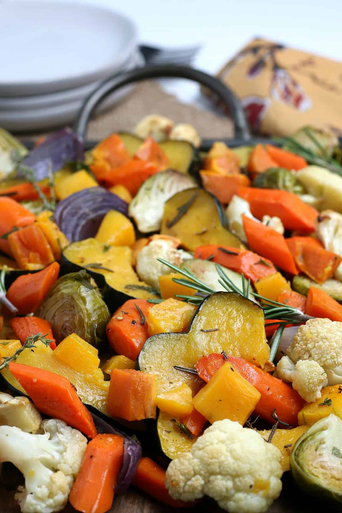 Tilted pan full of colorful roasted veggies with herbs.