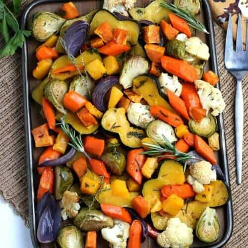 Looking down at a slew of colorful roasted fall vegetables on a tray.
