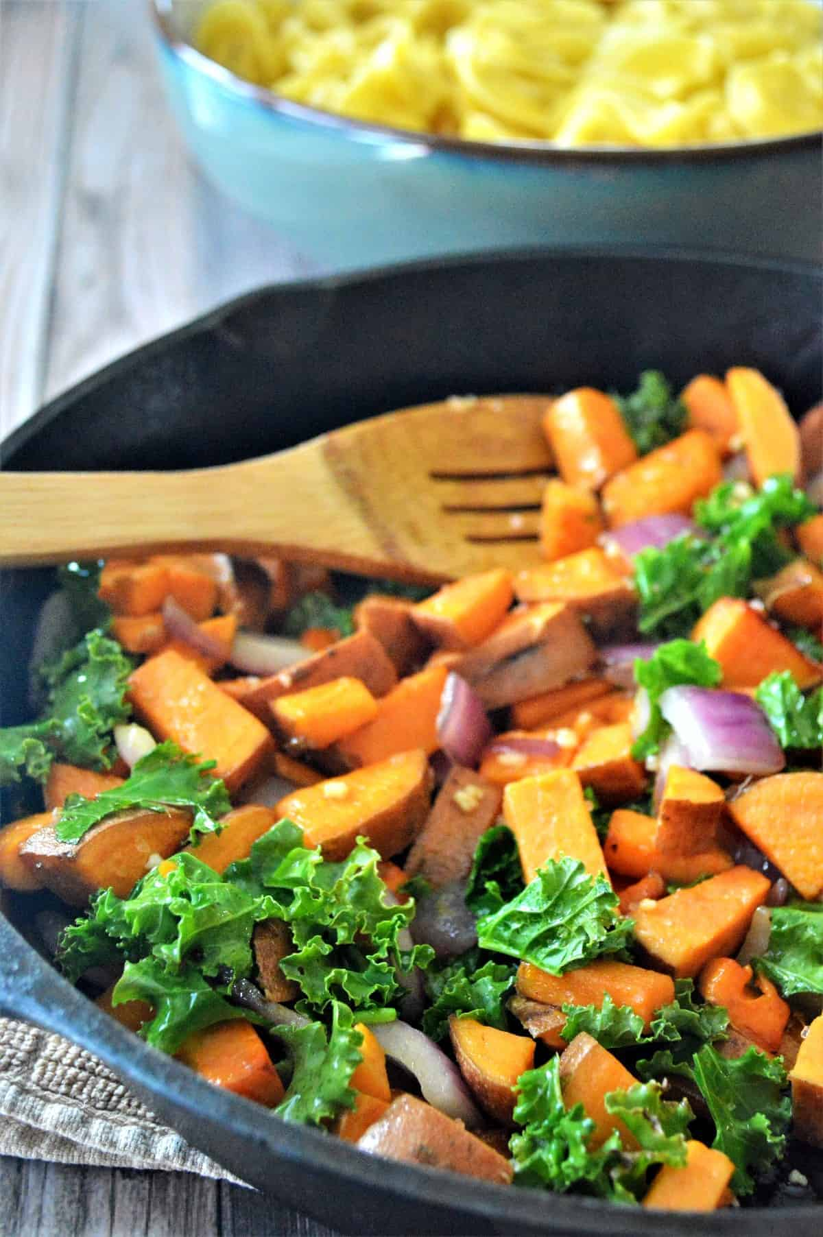 Skillet of vegetables and kale being cooked and stirred with a wooden spoon.