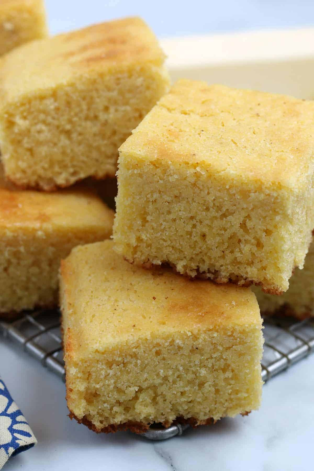 Close up of many squares of cornbread stacked on top of each other.