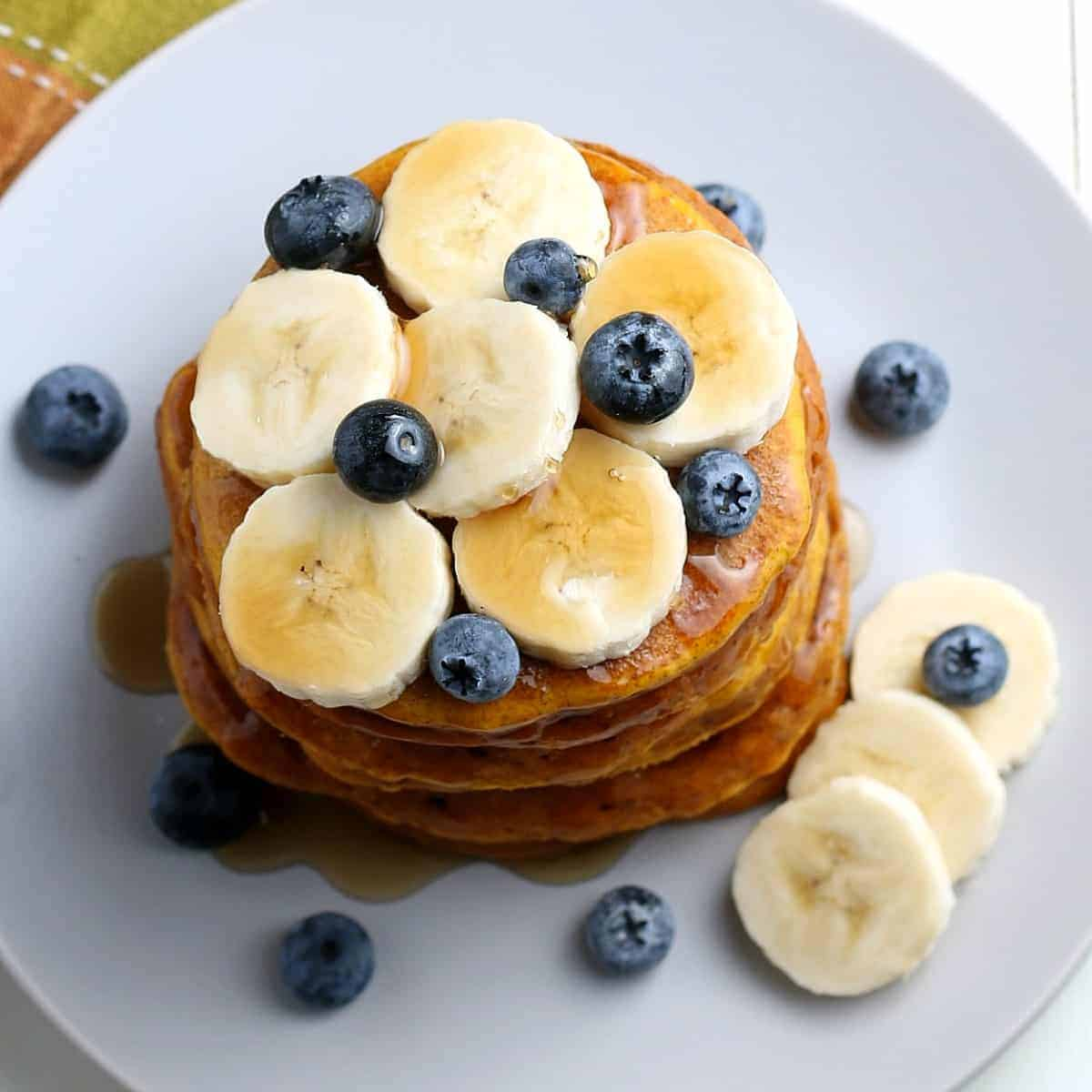 Five pancakes tilted towards the camera with syrup and fruit on top and scattered on the plate.