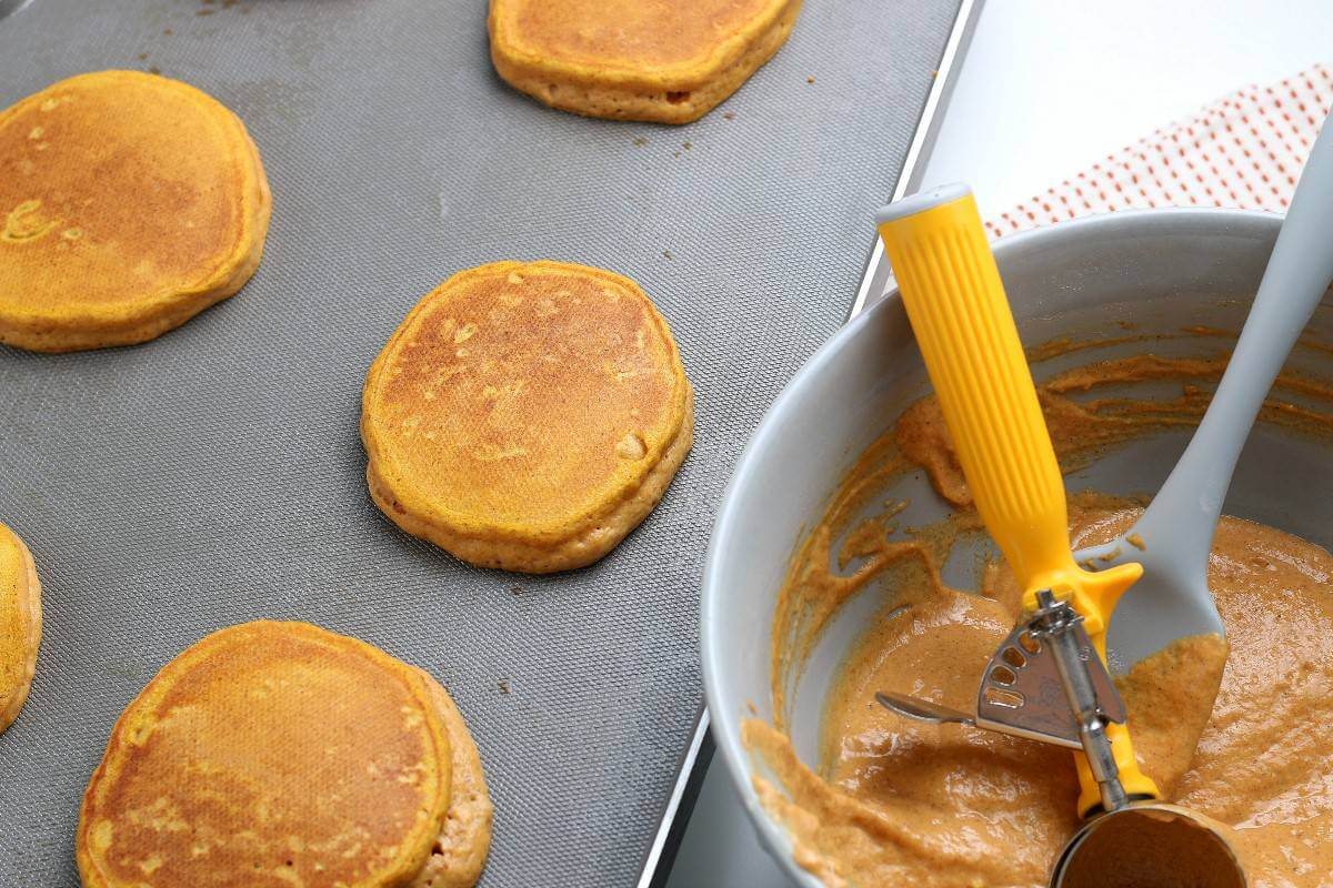 Batter in a bowl with scoop and pancakes flipped on a griddle.