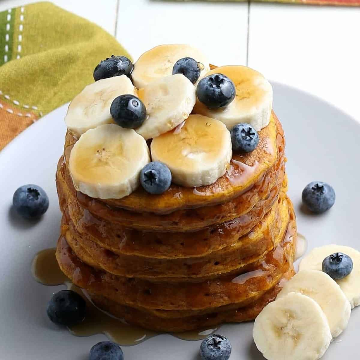 Stack of tilted pumpkin pancakes covered in syrup and bananas.