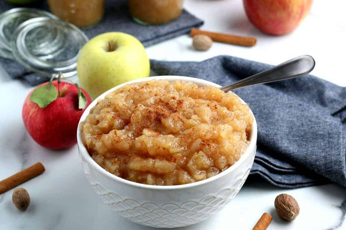 A full bowl of applesauce with a spoon inside.