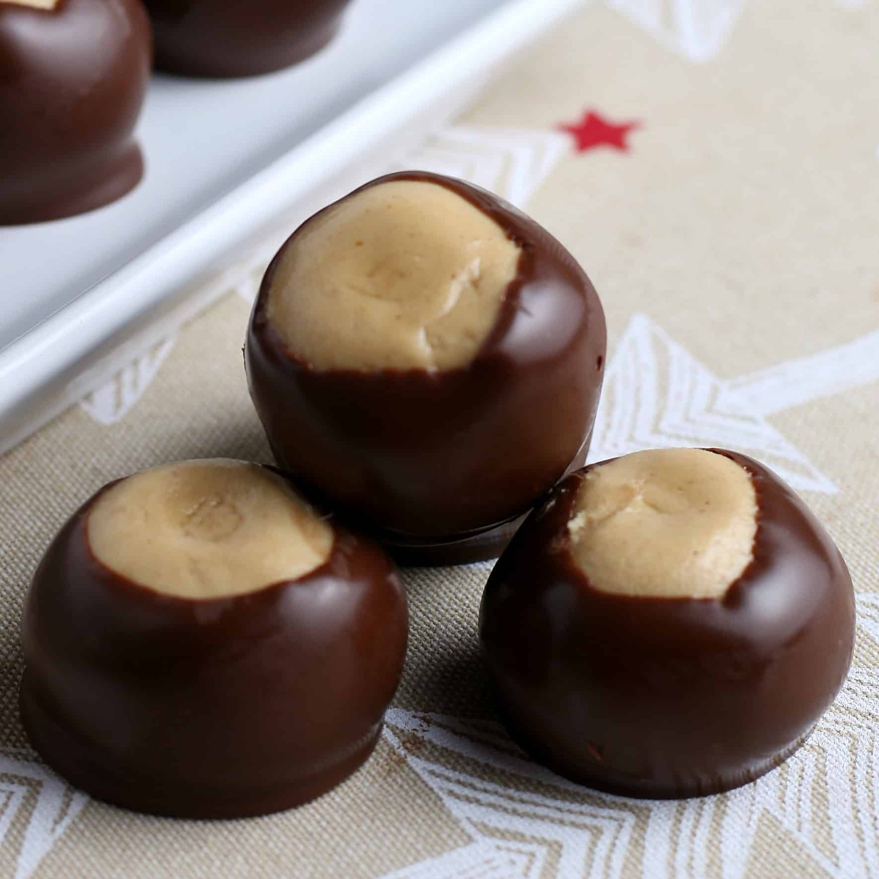 Three stacked peanut butter balls dipped in chocolate.