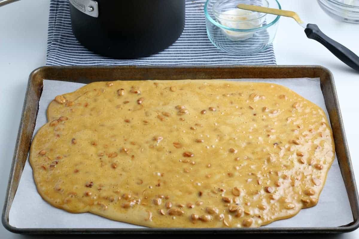 Peanut Brittle poured onto a parchment lined baking sheet.