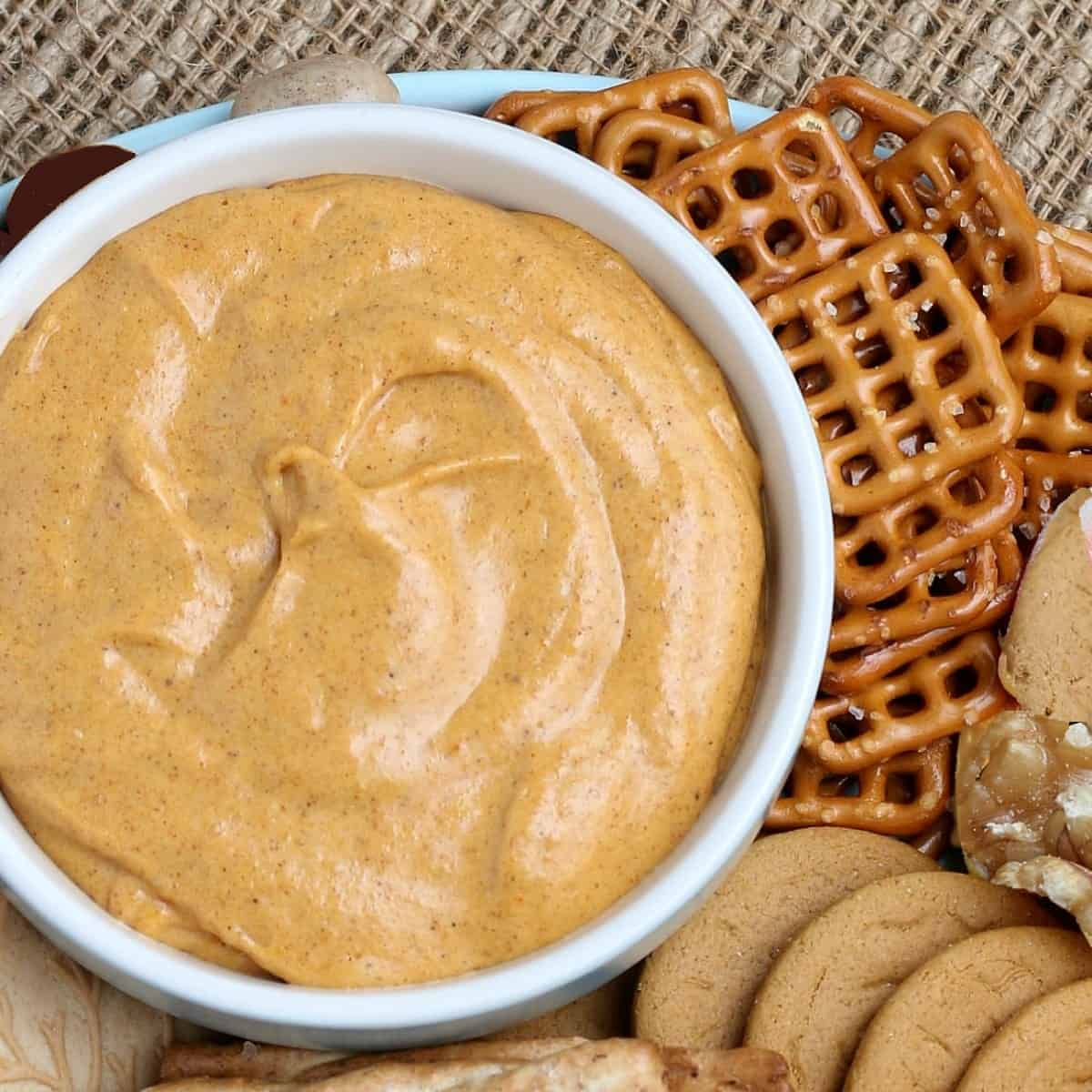 Overhead cropped bowl of pumpkin dip with cookies and nuts scattered around,