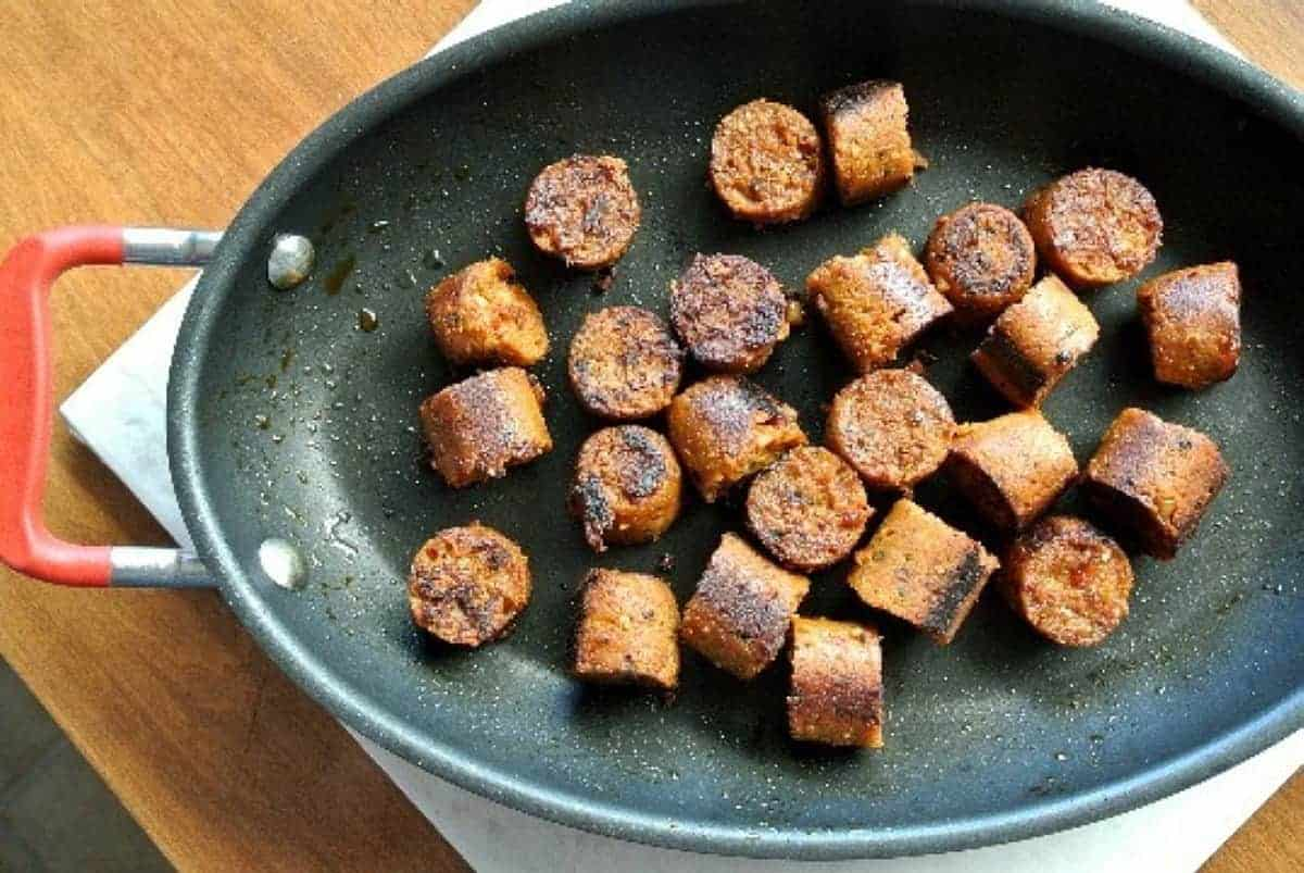 Overhead view of plant based sausage cuts being sautéd and browned.