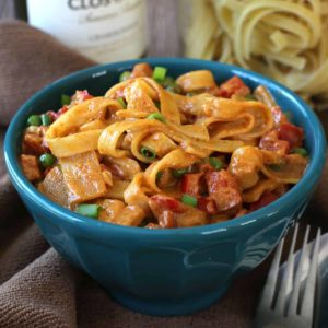 Creamy sauced pasta in a turquoise bowl.