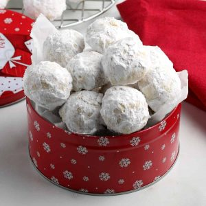 Red tin full of vegan snowball cookies which are covered in powdered sugar.
