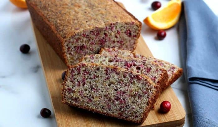 Wide photo with sliced vegan cranberry orange bread on a cutting board.
