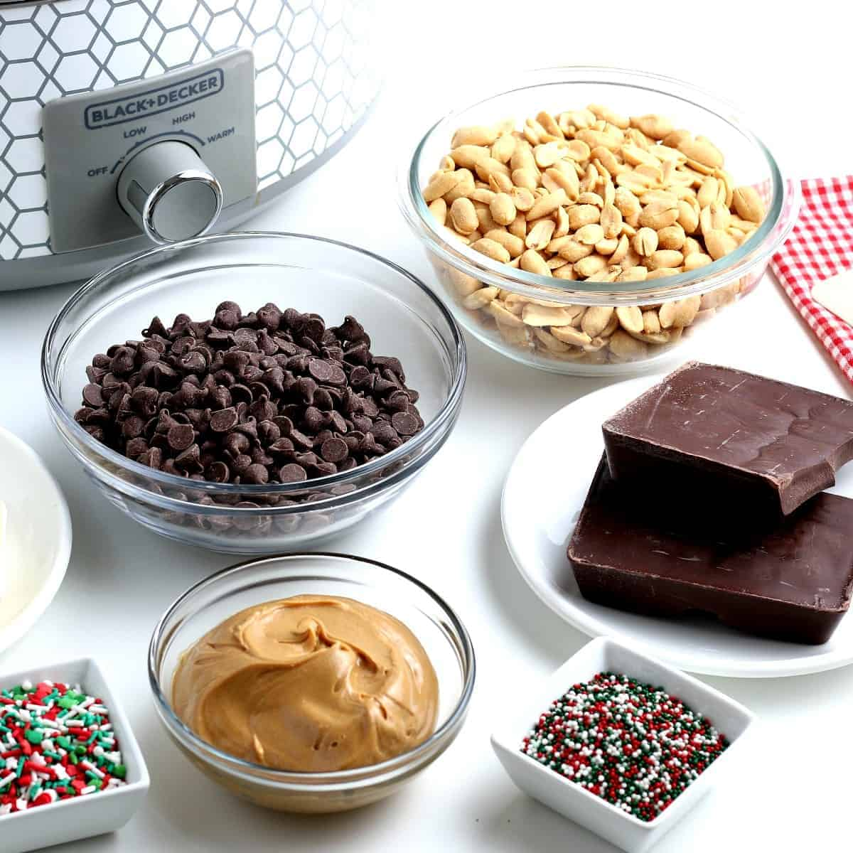 The five ingredients are sitting in front of a crock pot along with sprinkles.