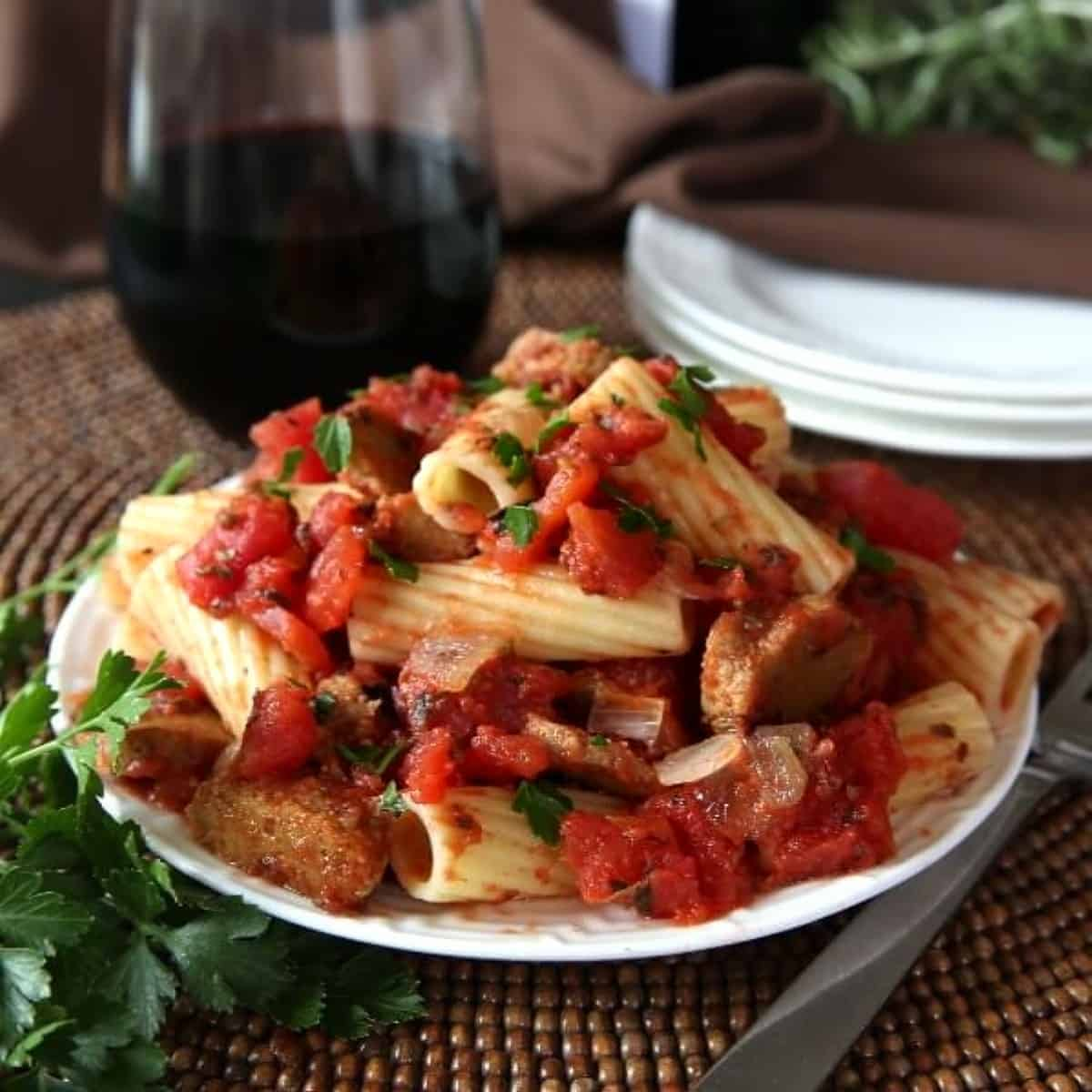 Seitan rigatoni pasta is piled on a white plate and mixed with a tomato sauce.