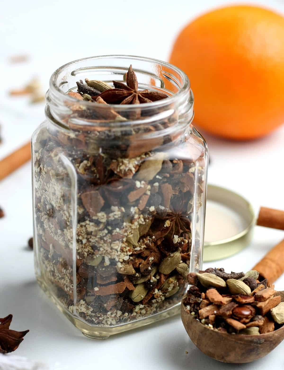 A spice jar and scoop gilled with homemade mulling spice mix.