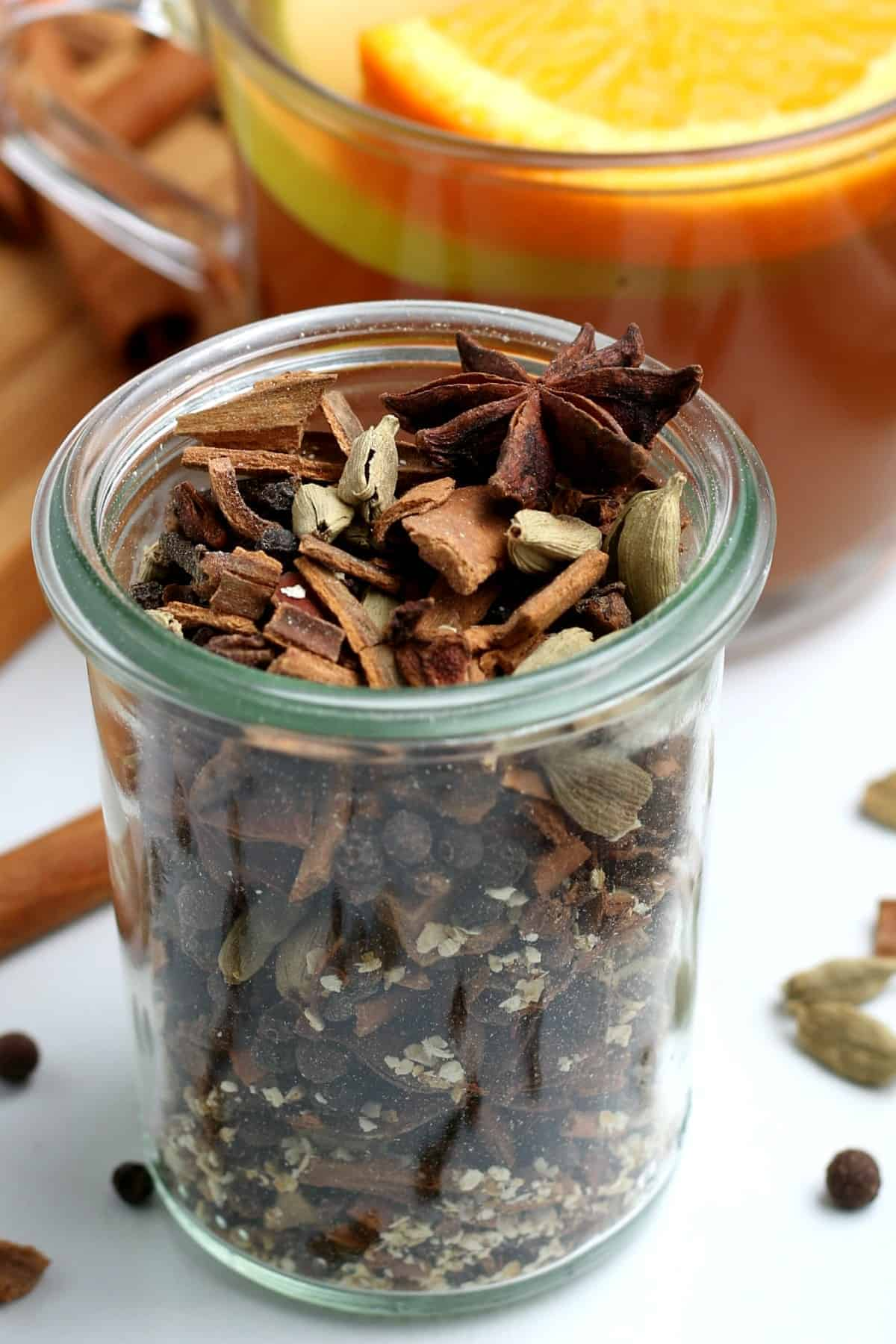 Close up glass jar filled with fall and winter spices.