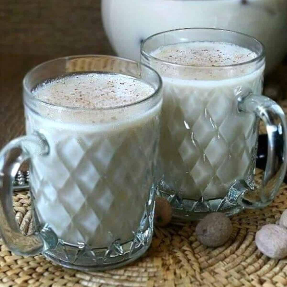 Two glass mugs filled with milk nog rum punch as one of our Vegan Christmas recipes.