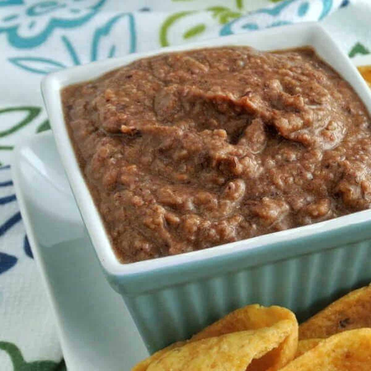 Black bean dip in a square bowl with chips on the side.