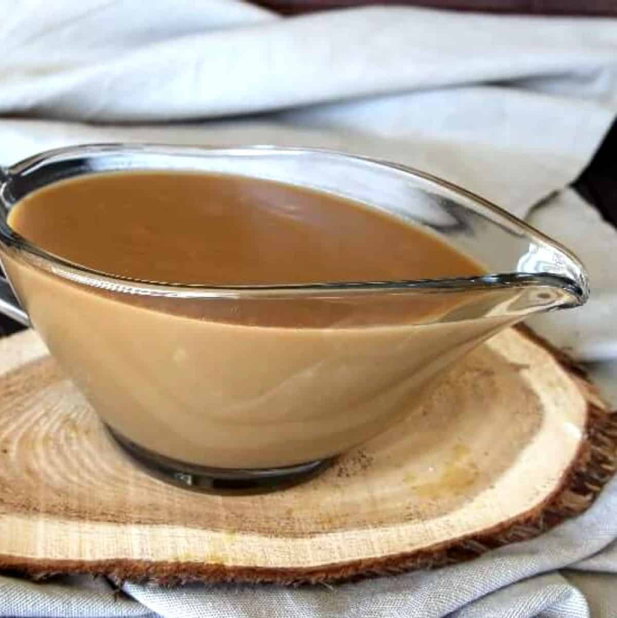 A Gravy Boat filled with gravy sitting on a wooden trivet.
