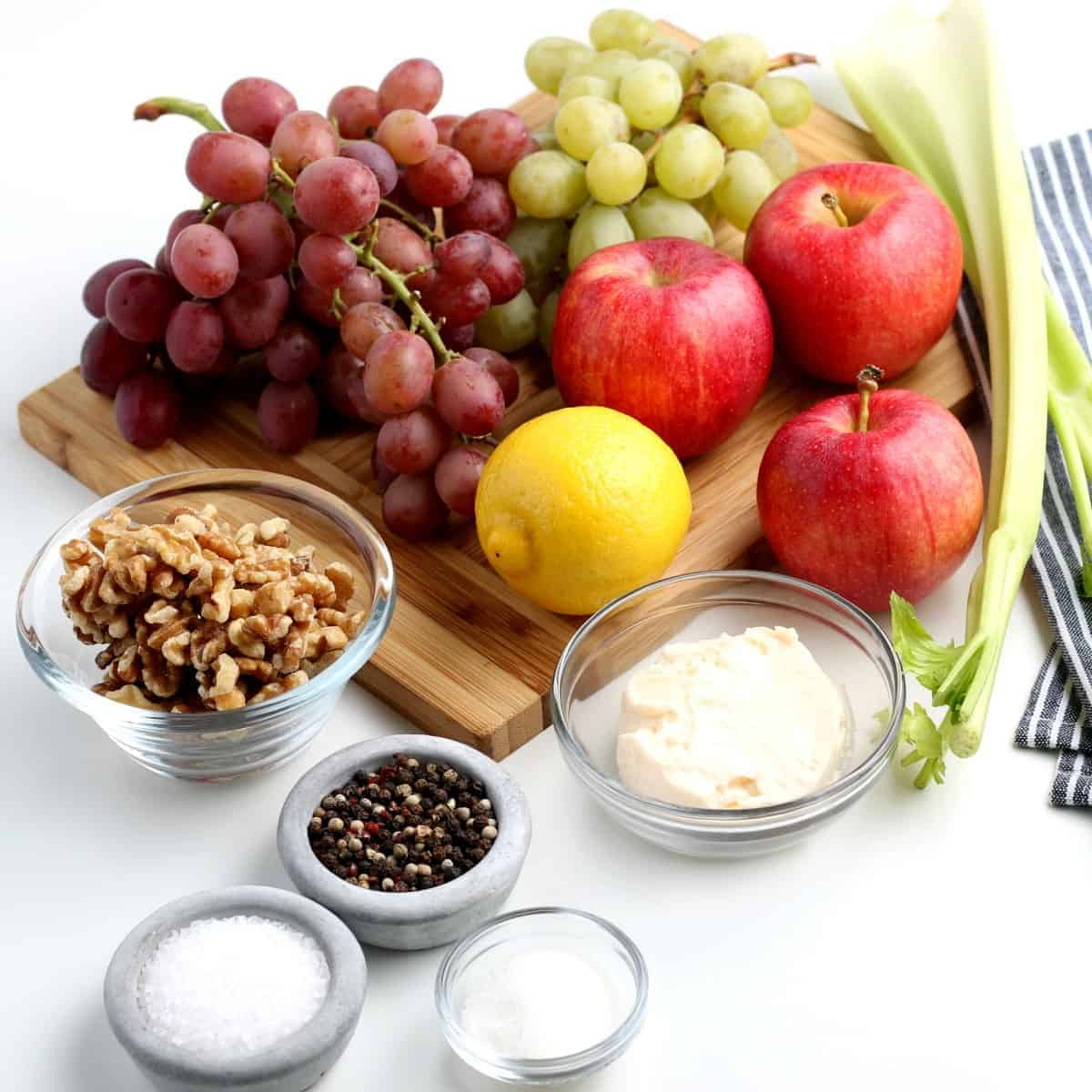 Ingredients for a fresh vegan Waldorf Salad are gathered together on a wooden board.