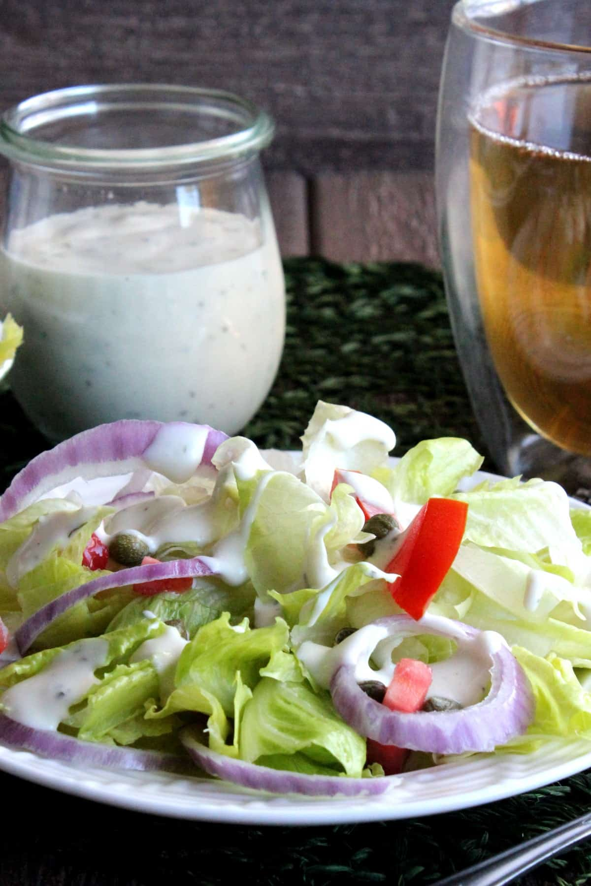 Plateful of a fresh salad drizzled with dairy free ranch dressing.