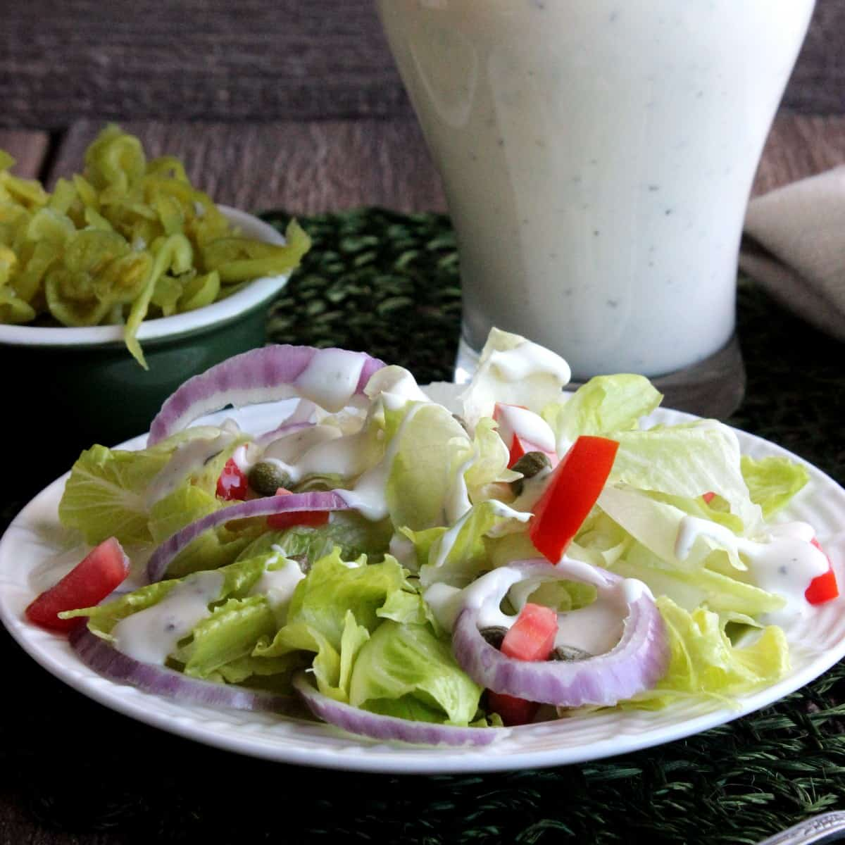 Fresh green salad on a white plate and drizzled witha salad dressing.