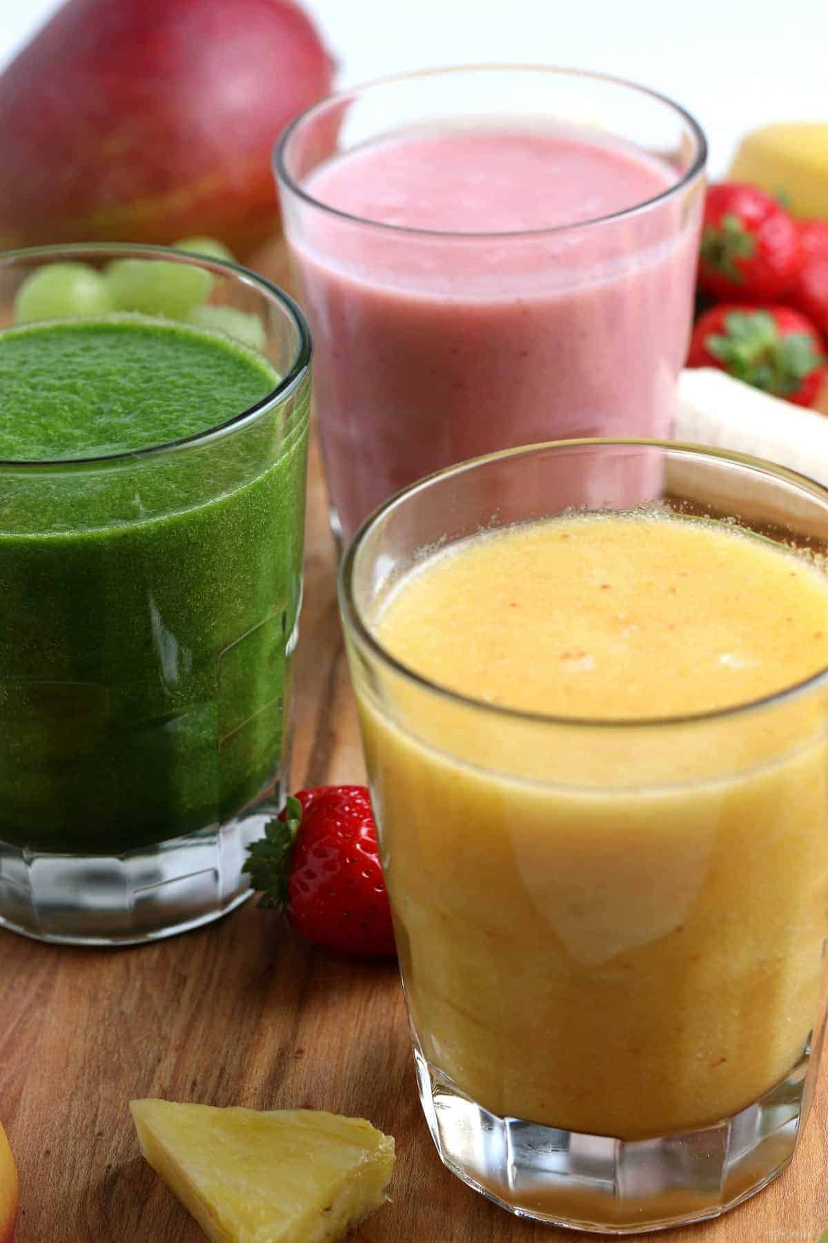 Close up photo of three glasses full of colorful smoothies.