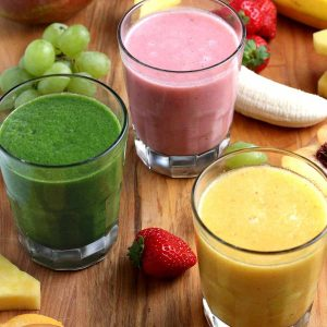 Three smoothies in different colors tilted towards the camera lens.