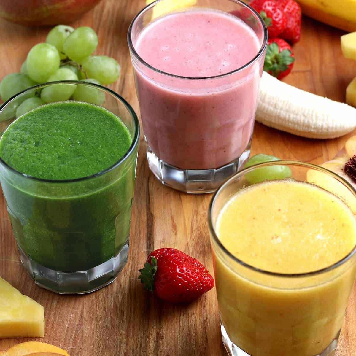 Healthy Vegan Smoothies in different colors tilted towards the camera lens.