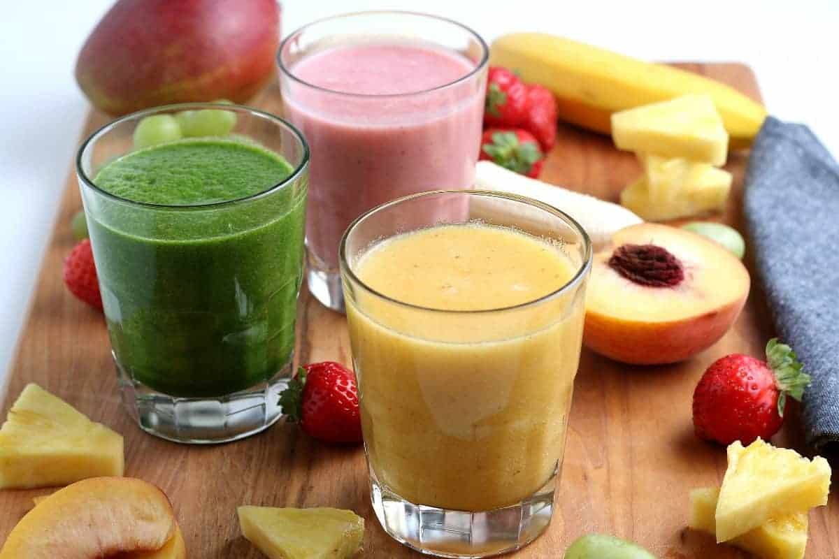 Wide photo with three glasses of healthy vegan smoothies using different fruits.