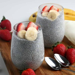 Two glasses are filled with chia seed pudding and they are topped with fresh fruit.
